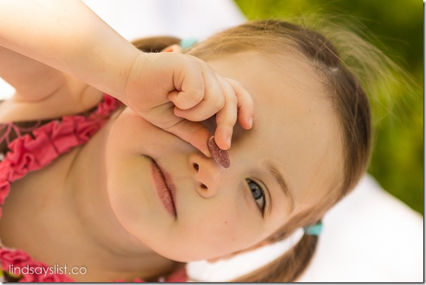 Young Girl Holding Almond Up To Eye