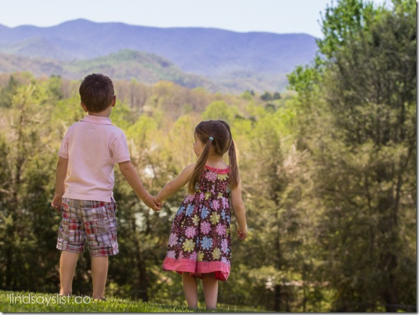 Young Boy and Girl holding hands looking at mountains